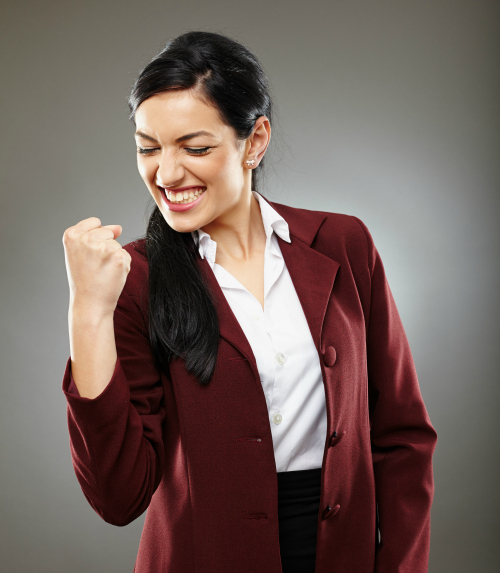 Happy hispanic businesswoman making a gesture of success